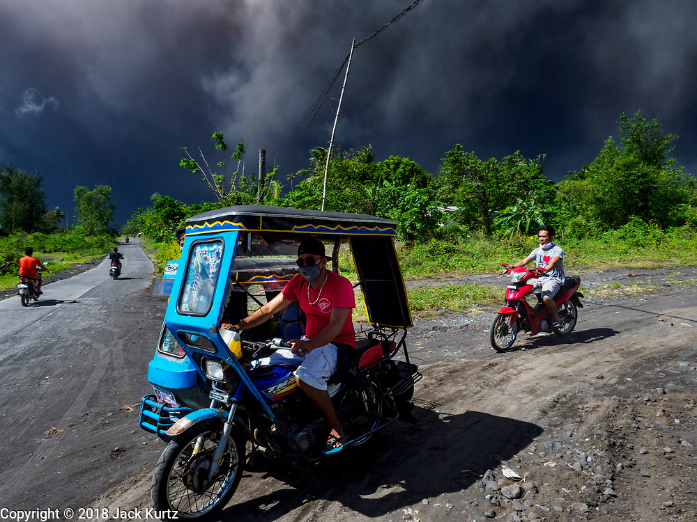 """22 JANUARY 2018 - CAMALIG, ALBAY, PHILIPPINES: People who live on the slopes of Mayon volcano rush out of the area after the a large eruption in the volcano Monday. There were a series of eruptions on the Mayon volcano near Legazpi Monday. The eruptions started Sunday night and continued through the day. At about midday the volcano sent a plume of ash and smoke towering over Camalig, the largest municipality near the volcano. The Philippine Institute of Volcanology and Seismology (PHIVOLCS) extended the six kilometer danger zone to eight kilometers and raised the alert level from three to four. This is the first time the alert level has been at four since 2009. A level four alert means a """"Hazardous Eruption is Imminent"""" and there is """"intense unrest"""" in the volcano. The Mayon volcano is the most active volcano in the Philippines. Sunday and Monday's eruptions caused ash falls in several communities but there were no known injuries.    PHOTO BY JACK KURTZ"""