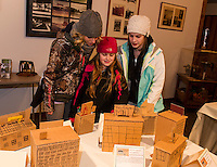 Carolyn Keenan shows her mother Cheryl and big sister Emma the Mill she made during the Elm Street School 3rd Grade Mill presentation Thursday evening.  (Karen Bobotas/for the Laconia Daily Sun)
