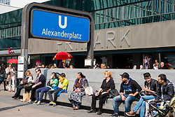 People sitting beside entrance to Alexanderplatz U Bahn station in Berlin Germany