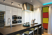 Modern kitchen with island and stools. Latest-generation appliances