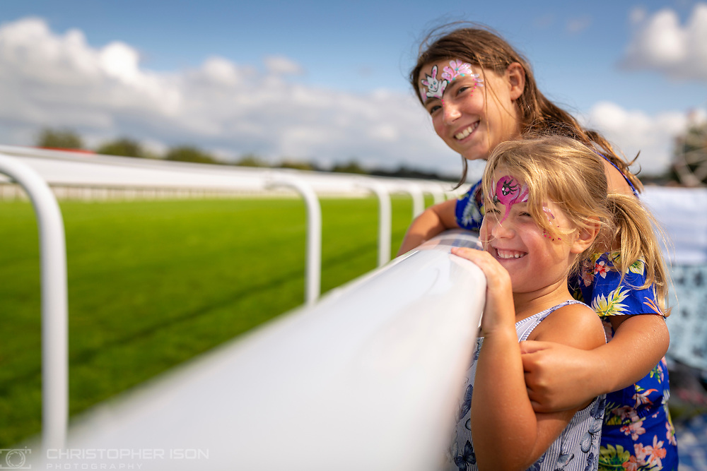 Sister with their faces painted watch the racing at Goodwood Racecourse.<br /> Picture date: Saturday August 28, 2021.<br /> Photograph by Christopher Ison ©<br /> 07544044177<br /> chris@christopherison.com<br /> www.christopherison.com<br /> <br /> IMPORTANT NOTE REGARDING IMAGE LICENCING FOR THIS PHOTOGRAPH: This image is supplied to the client under the terms previously agree. No sales are permitted unless expressly agreed in writing by the photographer.