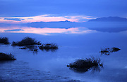 Winter clouds cast a chilling hue over the still waters of the Great Salt Lake in Utah, as a clear sky can be seen in the distance.