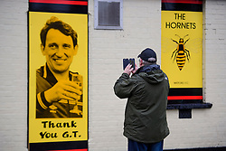 © Licensed to London News Pictures. 01/02/2017. Watford, UK. A fan takes pictures of Graham Taylor themed decorations on The One Bell pub, next to the funeral of former England football team manager Graham Taylor at St Mary's Church in Watford, Hertfordshire. The former England, Watford and Aston Villa manager,  who later went on to be chairman of Watford Football Club, died at the age of 72 from a suspected heart attack. Photo credit: Ben Cawthra/LNP