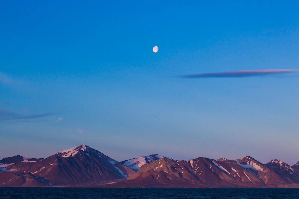 Moonrise over mountains on the coast in Bellsund, Spitsbergen, Svalbard.