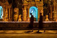 YANGON, MYANMAR - CIRCA DECEMBER 2017: Monks walking at the Shwedagon Pagoda in Yangon at night