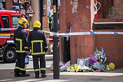 © Licensed to London News Pictures . 14/07/2013 . Manchester , UK . Two fire fighters watch over flowers and tributes left at the scene where a fire fighter, identified as Stephen Hunt, died while tackling a fire in a store-room of Paul's Hair World in Oldham Street, Manchester. Two 15-year-old girls arrested on suspicion of manslaughter. Photo credit : Joel Goodman/LNP