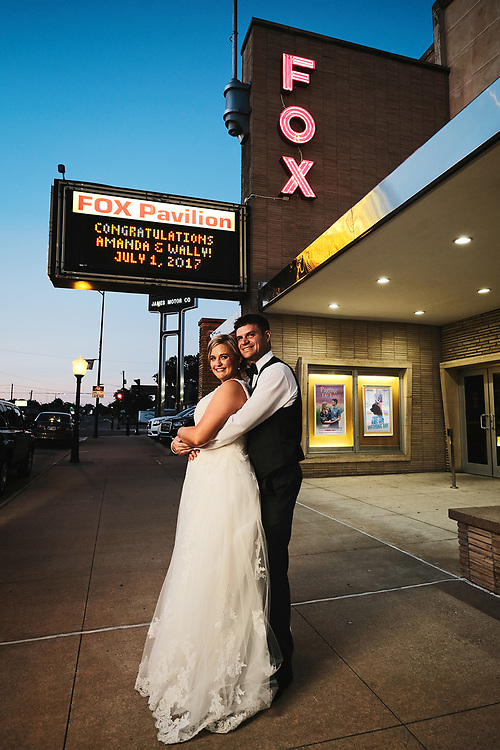 Oklahoma City Wedding photographer Dustin Schmidt photographs a newly married couple in front of the Fox Theatre in Hays, Kansas at dusk.