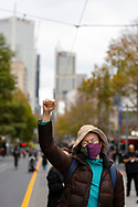 A woman wearing a facemask with her fist in the air marches through the CBD during a Black Lives Mater rally on 06 June, 2020 in Melbourne, Australia. This event was organised to rally against aboriginal deaths in custody in Australia as well as in unity with protests across the United States following the killing of an unarmed black man George Floyd at the hands of a police officer in Minneapolis, Minnesota. (Photo by Dave Hewison/ Speed Media)