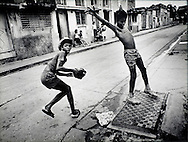 On the streets of Santiago, Cuba as a young baseball player uses a drain hole cover as first base, circa 1990s