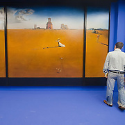 """MILAN, ITALY - SEPTEMBER 21:  A man and a woman admire """"Landscape with girl skipping rope"""", oil painting by Salvador Dali at the Exhibition preview at Palazzo Reale on September 21, 2010 in Milan, Italy. Dali is back in Milan with Il sogno si avvicina, an exhibition that takes place at Palazzo Reale  and that focus on the relationship between the great Spanish artist's visions and his favourite themes:  landscape, dream and desire."""