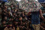 Rohingyas_10<br /> Decenas de hombres esperan bajo la lluvia algo para comer en el campo de refugiados de Balukhali.<br /> Diferentes ONGs reparten alimentos diariamente, pero hay tanta gente que  en algunos lugares se forman grandes colas. Soldados del ejército de Bangladesh y voluntarios controlan que nadie se salte el turno obligando a los refugiados a permanecer sentados. 28/09/2017.