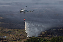 © Licensed to London News Pictures . 03/07/2018. Bolton, UK. A helicopter picks up water from reservoirs and dowses the fire as part of a combined firefighting effort. Fire-fighters continue to work to contain large wildfires spreading across Winter Hill as very high temperatures , changing winds and dry peat continue to exacerbate the problem . Photo credit: Joel Goodman/LNP