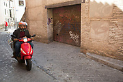 Man rides a moped through the streets in the old Moorish area of Albaicin, Granada, Spain. El Albayzín (also Albaicín or El Albaicín) is the autonomous community of Andalusia, Spain, that retains the narrow winding streets of its Medieval Moorish past. It was declared a world heritage site in 1984.
