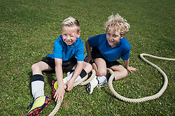 Two young boys resting on grass Tug-of-war