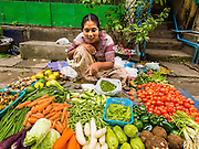 02 NOVEMBER 2014 - YANGON, MYANMAR: A vegetable vendor in the 38th Street morning market in downtown Yangon, Myanmar. The market is typical of morning markets in Yangon, a city coming out of more the 50 years of economic isolation. Most people still shop in markets because Yangon does not have as many grocery stores as Bangkok, Kuala Lumpur or many other large cities.     PHOTO BY JACK KURTZ