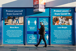 © Licensed to London News Pictures. 23/10/2020. Slough, UK. A man with blue headphones on walks past an empty shop with coronavirus safety advice covering the windows. Slough will move to Local COVID Alert Level: High (Tier 2) at 00:01 BST on Saturday 24th October 2020 after an increase in people infected with the COVID-19 coronavirus. Photo credit: Peter Manning/LNP