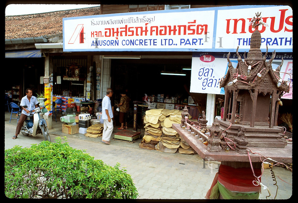 Traditional spirit house guards hardware store where raw rubber mats sit stacked at door; Phuket Thailand