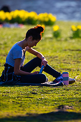 A woman rests on the grass as crowds enjoy the unseasonably warm and sunny weather in Regents Park, London. London, February 26 2019.