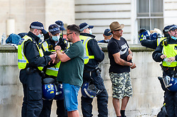 © Licensed to London News Pictures. 19/07/2021. LONDON, UK.  Police officers in Whitehall with arrested protesters at an anti-vaccine protest in Parliament Square, on what has been dubbed Freedom Day, when the UK government relaxed remaining coronavirus lockdown restrictions but the numbers of positive cases continues to increase daily and scientists concerned that restrictions have been eased too soon.  Photo credit: Stephen Chung/LNP