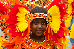 London, August 30th 2015. A little girl poses in her finery as revellers enjoy Family Day at the Notting Hill Carnival.
