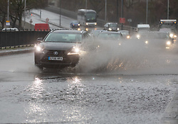 © Licensed to London News Pictures. 30/01/2021. London, UK. Cars and lorries hit flooding on the A4 in Hammersmith, West London this morning as the Met Office issue weather warnings for heavy rain and flooding for large parts of England. The Met office has issued weather warnings for much of the UK this weekend for snow, torrential rain and flooding with disruption to travel as the stormy weather continues. Photo credit: Alex Lentati/LNP