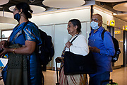 "Airline passengers recently arrived from India wait in line at Heathrow Airport's Terminal 5 transit concourse. The middle-aged travellers queue patiently after their long-haul flight and two believe that masks will protect themselves from airborne diseases and infections, not wishing to be exposed to Swine Flu or perhaps SARS, in a hectic public place where such bacteria can be transmitted from one human being to another. But a lady at the front of the queue has lowered her mask while the man at the back keeps his covering the mouth and nose. From writer Alain de Botton's book project ""A Week at the Airport: A Heathrow Diary"" (2009)."