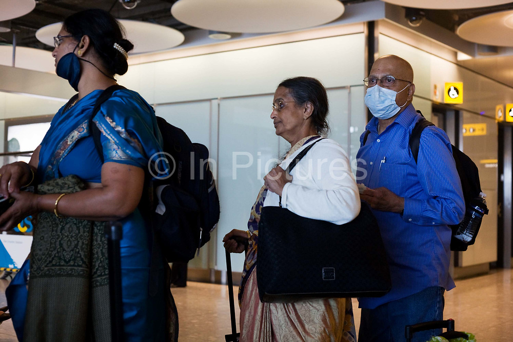 """Airline passengers recently arrived from India wait in line at Heathrow Airport's Terminal 5 transit concourse. The middle-aged travellers queue patiently after their long-haul flight and two believe that masks will protect themselves from airborne diseases and infections, not wishing to be exposed to Swine Flu or perhaps SARS, in a hectic public place where such bacteria can be transmitted from one human being to another. But a lady at the front of the queue has lowered her mask while the man at the back keeps his covering the mouth and nose. From writer Alain de Botton's book project """"A Week at the Airport: A Heathrow Diary"""" (2009)."""