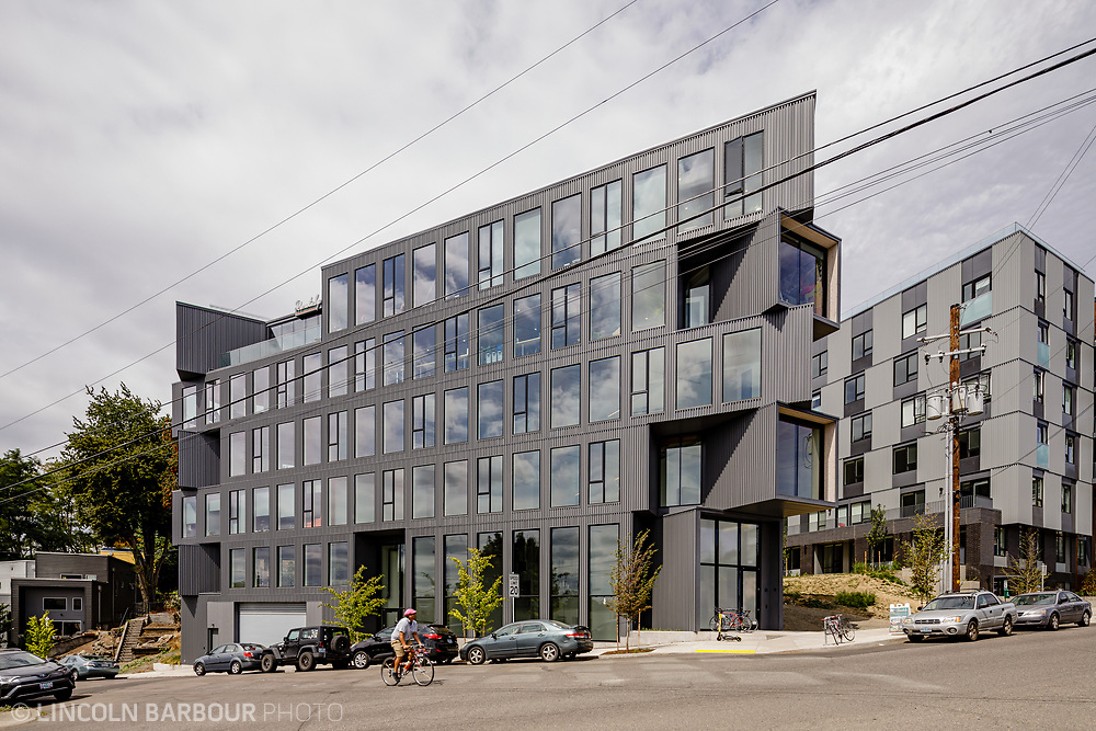 The Ironside Building in Portland, Oregon.  A cyclist rides up the hill in front of the geometric inspired building. Architectural photograph of the Flatiron building designed by Works Progress Architecture