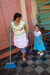 Central America, Nicaragua, Granada.  Woman and young daughter sweep sidewalk at market.