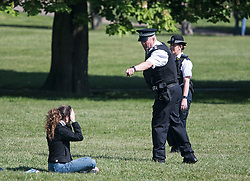 © Licensed to London News Pictures. 20/04/2020. London, UK. Police move a woman lying down on Primrose Hill, north London during a pandemic outbreak of the Coronavirus COVID-19 disease. The public have been told they can only leave their homes when absolutely essential, in an attempt to fight the spread of coronavirus COVID-19 disease. Photo credit: Ben Cawthra/LNP. Photo credit: Ben Cawthra/LNP