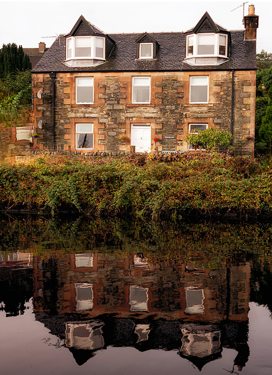 Black water of the Crinan Canal mirrors a house by its banks.