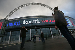 © Licensed to London News Pictures. 18/11/2015. London, UK French fans take a photo at the Bobby Moore statue outside  Wembley stadium as the French national motto of Liberté, égalité, fraternité is displayed ahead of the England v France football match. Photo credit: Peter Macdiarmid/LNP