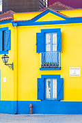 Brightly coloured blue and yellow facade, balconies, shutters and hydrant in Cais dos Botiroes by the marina at Aveiro, Portugal