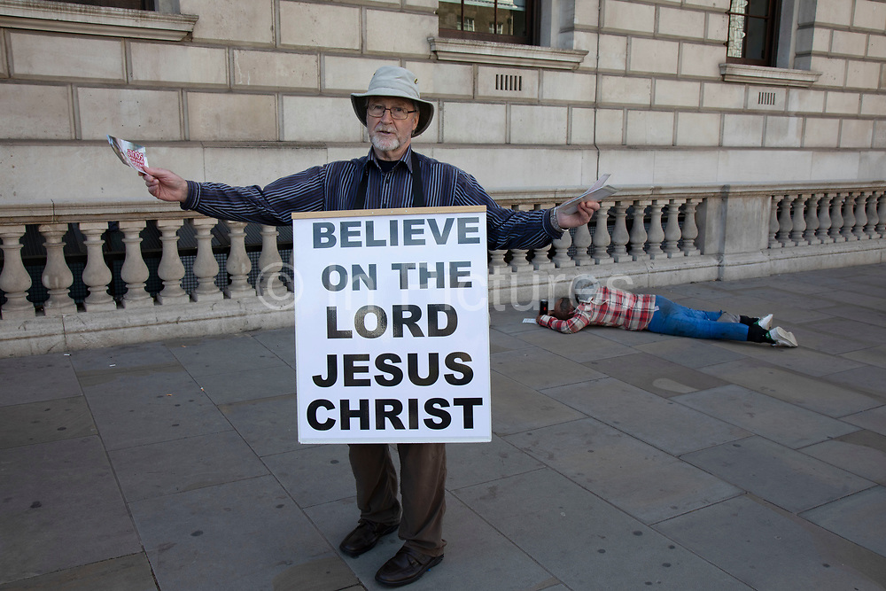Street preacher extoling the ways of the Lord Jesus Christ on Whitehall, while a street drinker is passed out on the pavement behind him on 17th June, 2019 in London, England, United Kingdom.