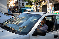 © Licensed to London News Pictures. 16/08/2020. Beirut, Lebanon. A man drives his car with a smashed windscreen in the Karantina district of Beirut which has been badly destroyed following the huge explosion in Beirut Port on 4 August. Photo credit : Tom Nicholson/LNP