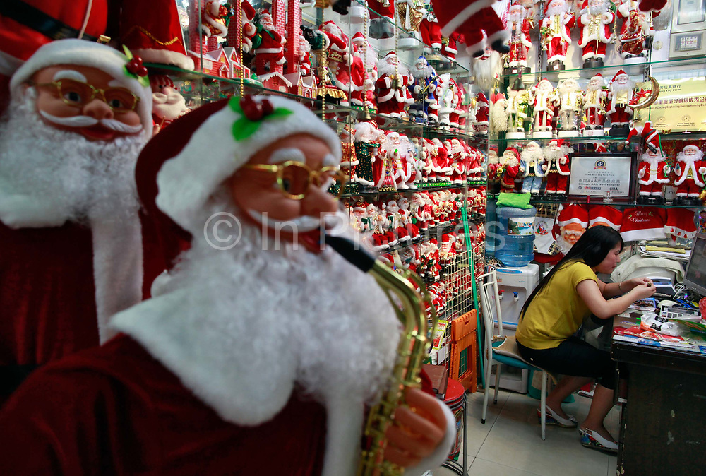 A woman sits in a stall selling Santa Claus figures at the Yiwu International Trade City in Yiwu, Zhejiang Province, China on Sunday, 11 September 2011.   As the trading hub for small and medium manufacturers and exporters in the Yangtze River Delta region, Yiwu faces an uncertain future as export orders decline due to the slow economic recoveries of China's two largest trading partners, Europe and the United States