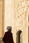 Rear view of senior man in traditional clothing nearby Hassan II Mosque in Casablanca, Morocco