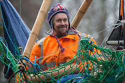 Denham, UK. 8th December, 2020. Dan Hooper, widely known as Swampy during the 1990s, smiles as he holds a lock-on arm tube on a bamboo tripod positioned in the river Colne. The climate and roads activist had occupied the tripod the previous day in order to delay the building of a bridge as part of works for the controversial HS2 high-speed rail link and a large security operation involving officers from at least three police forces, the National Eviction Team and HS2 security guards was put in place to facilitate his removal.