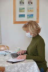 Covid 19 - Woman working from home wearing a face mask, UK March 2020. Posed by model