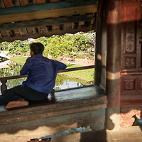 A local hangs out in the early morning on Thanh Toan bridge in Thanh Toan village outside of Hue, Vietnam.