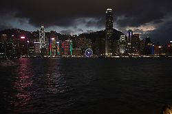 Hong Kong, China skyline and Hong Kong Observation Wheel lit up with a stormy evening sky viewed across Victoria Harbor with boats on water in foreground.