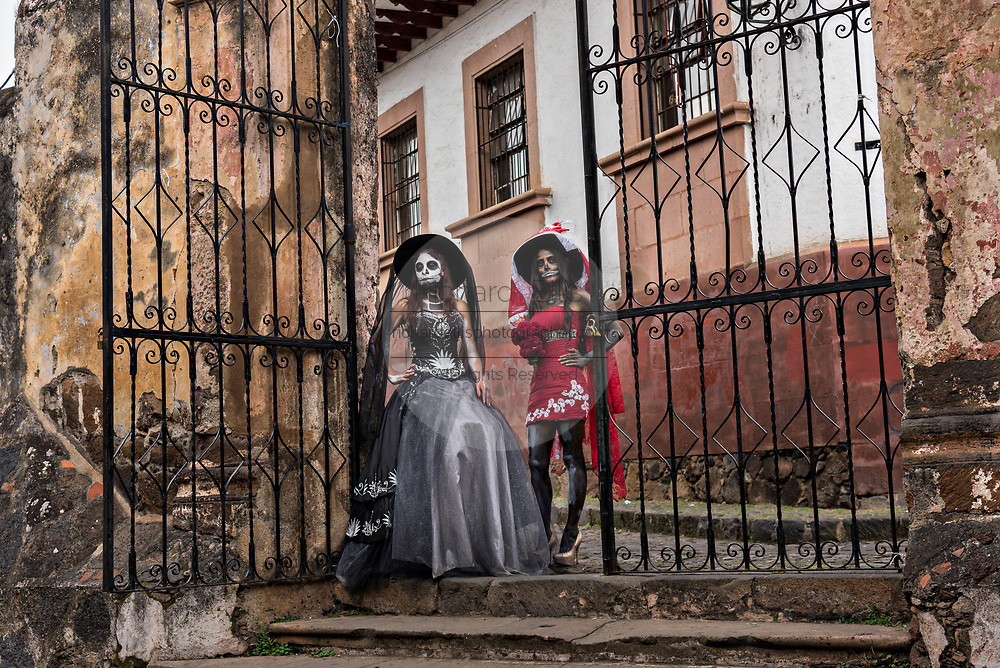 Young Mexican women dressed in La Calavera Catrina costumes at the Templo del Sagrario during the Day of the Dead or Día de Muertos festival October 31, 2017 in Patzcuaro, Michoacan, Mexico. The festival has been celebrated since the Aztec empire celebrates ancestors and deceased loved ones.
