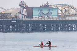 Licensed to London News Pictures. 06/09/2021. Brighton, UK. Paddle boarders cool off from the hot sun in the sea at Brighton Beach, East Sussex as weather forecaster predict a mini-heatwave for September this week with temperatures hitting over 29c tomorrow. Photo credit: Alex Lentati/LNP