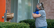 Head Start bus driver Sue Pierringer gives a virtual hug after delivering food to a family. The food from Little John's restaurant is being delivered to families with food insecurities during the COVID-19 pandemic. (Photo © Andy Manis)