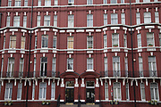 Mansion style building painted ox blood red in Marylebone in London, England, United Kingdom. A mansion block refers to a block of flats or apartments designed for the appearance of grandeur.