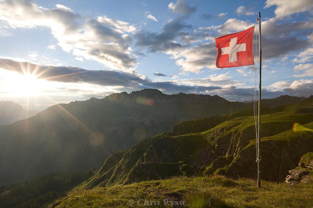 Swiss flag atop cliff face near dusk, Swiss Alps, Flumserberg, Sarganserland, Switzerland