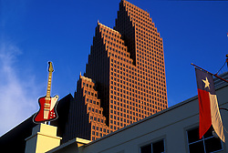 Daytime Houston cityscape featuring the Bank of America Center (formerly known as the RepublicBank Center and NationsBank Center) and the 35-foot replica of the Stevie Ray Vaughan Gibson Firebird guitar at Hard  and a Texas State Flag.