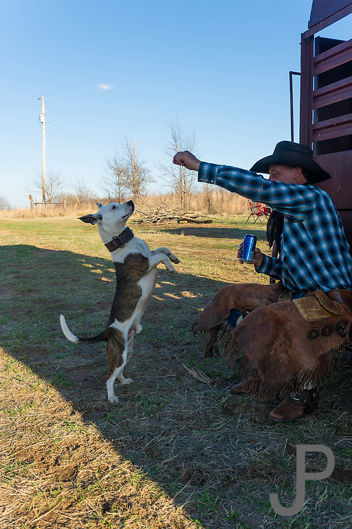 Brian Mayfield teaches his dog to jump while camping at the Packsaddle Wildlife Managment area south of Arnett, Oklahoma.