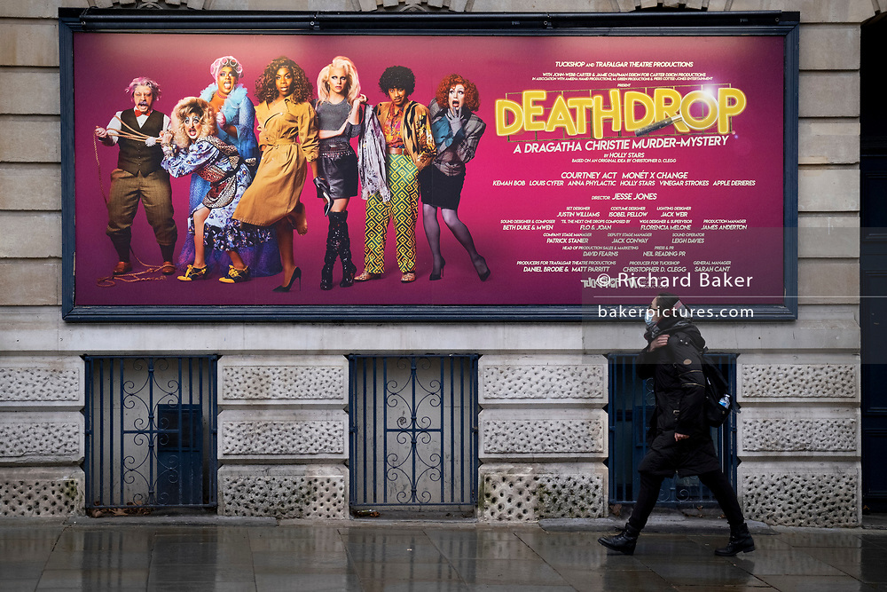 The day after the government introduced a third Coronavirus pandemic national lockdown, effectively a Tier 5 restriction, a masked woman walks beneath a West End theatre poster for the Agatha Christie murder mystery, 'Deathdrop', as the capital experiences a grim post-Christmas and millions of Britons are told to stay at home, on 5th January 2021, in London, England.