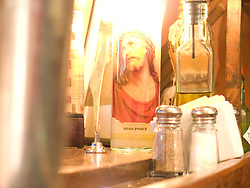 A votive candle holder with the image of Jesus Chris on it illuminates a section of a bar in a restaurant. Adams Morgan, Washington, DC